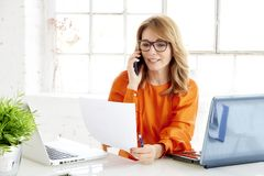 Shot of attractive mature businesswoman using her mobile phone and talking with her client royalty free stock photo