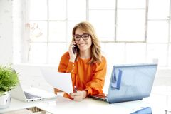 Shot of attractive mature businesswoman using her mobile phone and talking with her client stock photos