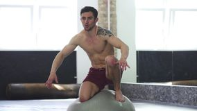 Young handsome ripped male athlete balancing on a fitness ball stock footage