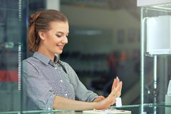 Shot of attractive young woman out shopping for jewelry. Girl lookin at he hand trying to choose between two rings Stock Images