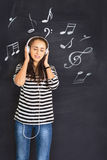 A shot of attractive young woman standing in front of a blackboa. Rd with musical notes drawn on and listening to music on headphones Stock Photo