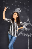 A shot of attractive young woman standing in front of blackboard Stock Image