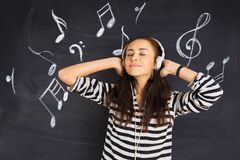A shot of attractive young woman standing in front of blackboard. A shot of attractive young woman standing in front of a blackboard with musical notes drawn on Royalty Free Stock Image