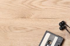 Shot of audio cassette and earphones in right corner over wooden surface. Music and revolution. Musical objects. Selective focus. stock image