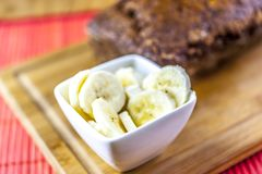 Shot of banana bread with bananas slices. Shot of fresh baked banana bread with some bananas slices on the wooden desk stock photography