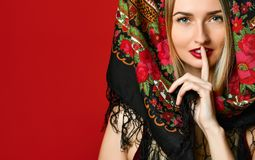 Shot of beautiful female with long blonde hair wears kokoshnik cap and patterned shawl, shows hush sign royalty free stock image