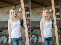 Shot of beautiful girl near an old wooden fence. Stylish look wear: white basic top, denim jeans. Country style farmer Stock Photo