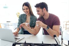 Beautiful lovely young couple using their laptop and having breakfast in the kitchen at home stock image