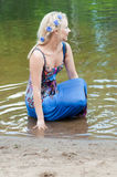 Shot of beautiful woman sitting in the pond Royalty Free Stock Photos