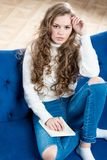 Shot of a beautiful woman in a sweater and jeans on the couch Royalty Free Stock Image