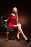 Shot of beautiful woman wearing red dress sitting Stock Photography