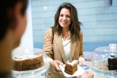 Beautiful young businesswoman buying portion of delicious homemade carrot cake in the coffee shop. Shot of beautiful young businesswoman buying portion of royalty free stock image