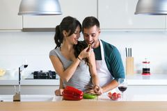 Beautiful young couple having romantic moments, woman feeding her husband with green pepper and smiling in the kitchen. royalty free stock images