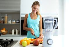 Beautiful young sporty woman cutting some vegetables and fruits while listening to music in the kitchen. Shot of beautiful young sporty woman cutting some stock image