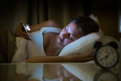 Beautiful young woman awake using smartphone in bedroom at night. Mobile phone abuse concept. Shot of beautiful young woman awake using smartphone in bedroom at royalty free stock photo
