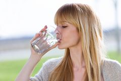 Beautiful young woman drinking water glass in the park. royalty free stock images