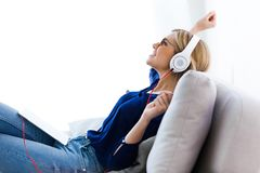 Beautiful young woman listening to music with her digital tablet at home. Shot of beautiful young woman listening to music with her digital tablet at home Stock Photos