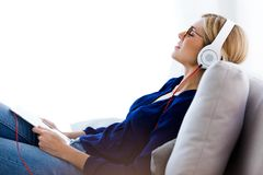 Beautiful young woman listening to music with her digital tablet at home. Shot of beautiful young woman listening to music with her digital tablet at home Royalty Free Stock Photo