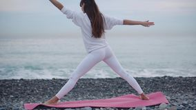 Yoga practice on sea shore. Shot from behind of a woman in white doing Warrior pose standing on a red yoga mat on pebble beach shore. Finding harmony and stock video