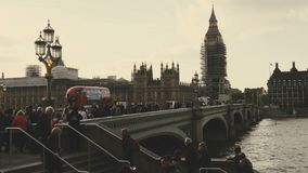 Shot of Big Ben and houses of Parliament during conservation refurbishment, people and traffic on Westminster br Bridge. Sliding shot from right to left of Big stock video footage