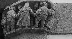 Dancing. Shot in black and white, detail on the sculpture on the  capital facade of this historic building representing some characters. Set in Sitges, Garraf Royalty Free Stock Photos