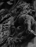 Fierce lion upon human heads. Shot in black and white, detail on the sculpture on the facade of this historic building representing an historic shield. Set in El royalty free stock photo