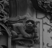 Monkey looking far beyond. Shot in black and white, detail on the sculpture on the facade of this historic building representing some characters / animals / Stock Image