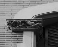 Birds standing by the window. Shot in black and white, detail on the sculpture on the facade of this historic building representing some characters / animals / Stock Image