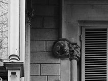 The little dragon is standing by the window. Shot in black and white, detail on the sculpture on the facade of this historic building representing some Stock Photo