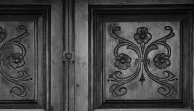 Flower wood on the main door. Shot in black and white, detail on the sculpture on the facade of this historic building representing some characters / animals / Royalty Free Stock Photos