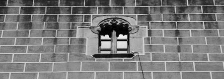 Small window with two angels. Shot in black and white, detail on the sculpture on the facade of this historic building representing some characters / animals / Stock Photos