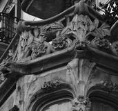 Angry dragons surrounded by flowers. Shot in black and white detail on the sculpture on the facade of this historic building representing some characters / Royalty Free Stock Images