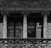 Three decorative columns. Shot in black and white detail on the sculpture on the facade of this historic building representing some characters / animals / plants Stock Photos