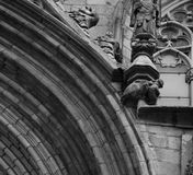 Strange creature on the main arcade. Shot in black and white detail on the sculpture on the facade of this historic building representing some characters / Royalty Free Stock Photography