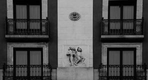 Naked children among windows. Shot in black and white detail of the sculpture on the facade of this historic building representing some characters / animals / royalty free stock images