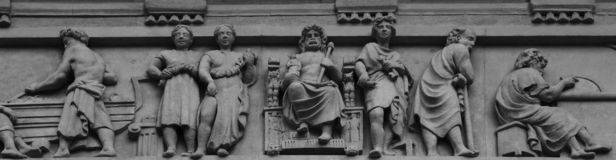 Symbolic scene with many characters part 5. Shot in black and white detail of the sculpture on the facade of this historic building representing some characters royalty free stock photography