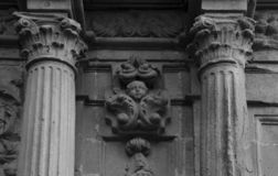 Child bust between the columns. Shot in black and white detail of the sculpture on the facade of this historic building representing some characters / animals / stock image