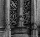 Characters on the column. Shot in black and white detail of the sculpture on the facade of this historic building representing some characters / animals / plants stock photography