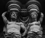Half naked couple on top. Shot in black and white, detail on the sculpture on the facade of this historic building representing some characters. Set in Bilbao Royalty Free Stock Image