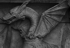 Dragon with fierce smile. Shot in black and white, detail on the sculpture on the facade of this historic building representing some characters, set in Zaragoza stock images