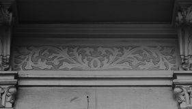 Nice floral detail among the columns. Shot in black and white detail on the sculpture on the facade of this historic building representing some flowers. Set in Stock Images