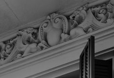 Two dragons facing each other. Shot and black and white, detail on the sculpture on the facade of this historic building representing some plants / flowers / Royalty Free Stock Photo