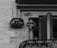 Character playing the violin. Shot and black and white, detail on the sculpture on the facade of this historic building representing some plants / flowers / Royalty Free Stock Photos