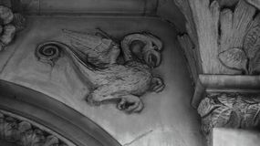 Flying creature. Shot in black and white. Detail on the sculpture on the facade of this historic building, representing a strange winged creature. Set in royalty free stock photo