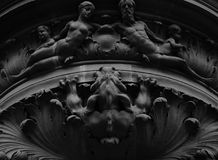 Swedish monster. Shot in black and white. Placed on the facade of this historic building, sculpture representing a strange animal attacking  a family. Set in Royalty Free Stock Photography