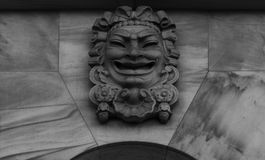 Theatrical face 2. Shot in black and white. Placed on the facade of this historic building, sculpture representing a theatrical character. Set in Eixample Royalty Free Stock Images