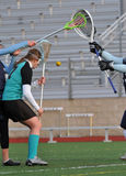 Shot blocked. High School girls varsity lacrosse player checked before she can make a shot Royalty Free Stock Photography
