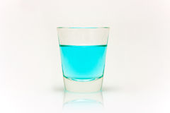 Shot of Blue. A shot glass filled with a blue liquid Royalty Free Stock Photos