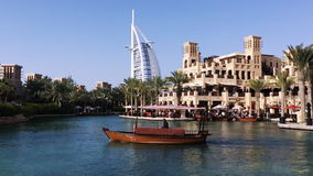 Shot of a boat moving in lake with the Burj Al Arab Hotel in background, Dubai, United Arab Emirates stock footage