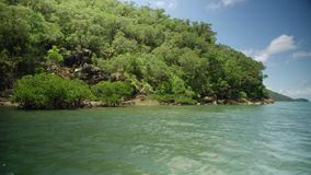 Sailing through an uninhabited island. A shot from a boat that shows an uninhabited island.  A white boat is seen from a far stock video footage